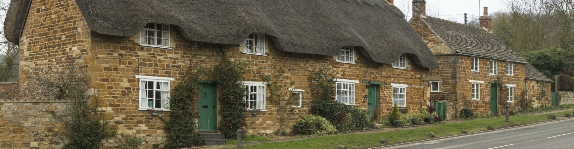 A row of picturesque thatched houses in a rural area which are insured under Acres Insurance's household insurance
