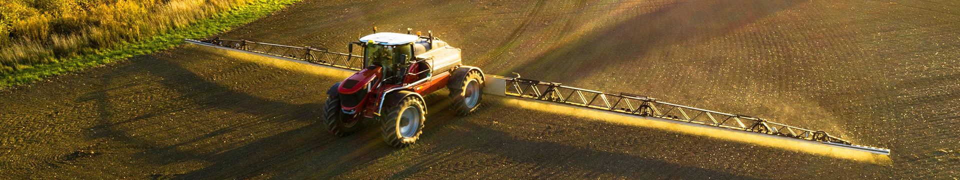 A tractor spraying a field with fertiliser close to the head office of Acres Insurance Brokers